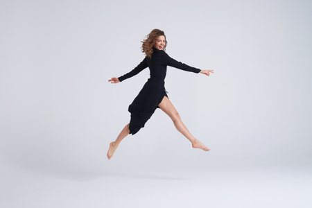 Full-length shot of jumping woman in black dress