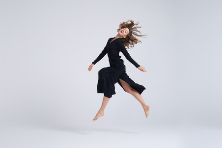 Full-length shot of young attractive woman hovering in the air Stock Photo