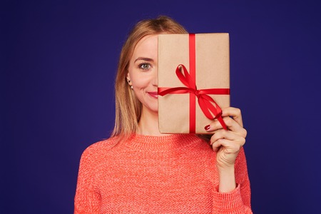 woman smiling and hiding face behind gift box