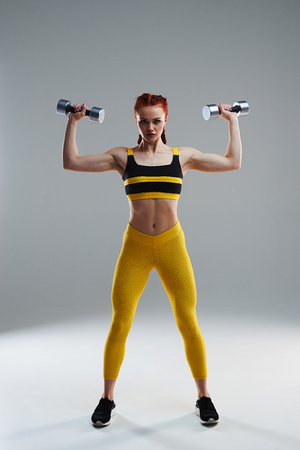 full lengths of young rude woman with dumbbells