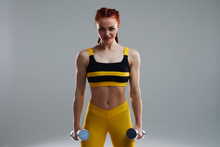 rude sportswoman standing with dumbbells
