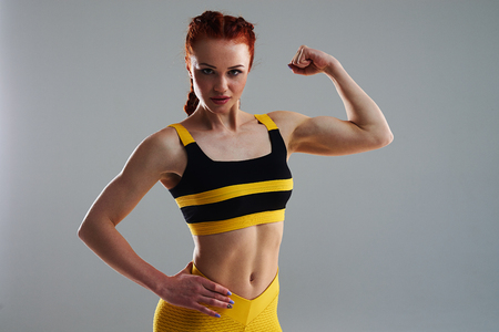 young woman posing and showing biceps