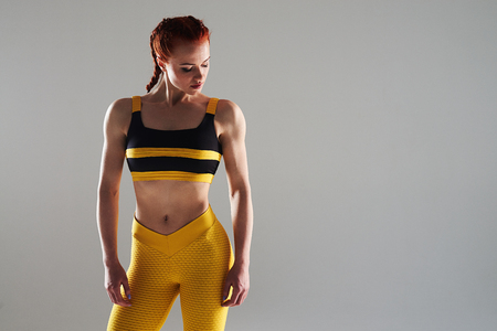 young woman in sportswear posing in studio