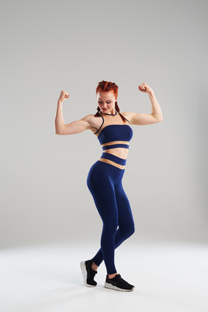 fit woman in blue sportswear posing in studio Stock Photo