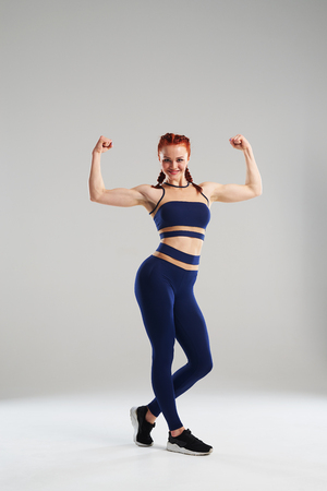 sportswoman in blue sportswear showing biceps