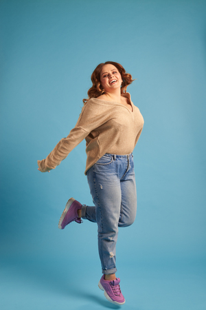 Plus-size woman jumping in excitement at studio Stock Photo