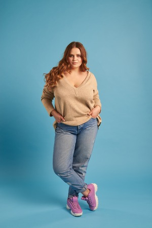 Confident plump girl in jeans and sweatshirt posing at studio