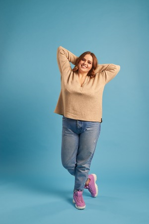 Joyful plus-size girl posing with arms above her head