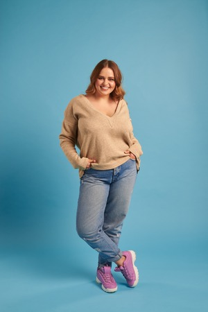 Carefree curvy girl with hands in pocket posing at studio