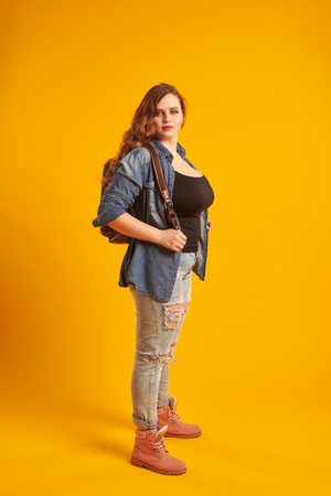 Confident curvy girl in denim jacket with backpack looking at ca Zdjęcie Seryjne