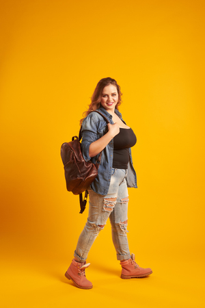 Smiling plus-size girl holding backpack walking at studio Zdjęcie Seryjne