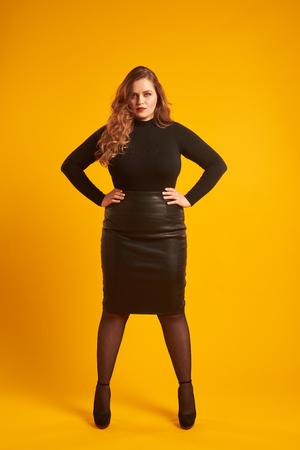 Fiduciosa ragazza curvy in piedi con le mani sui fianchi
