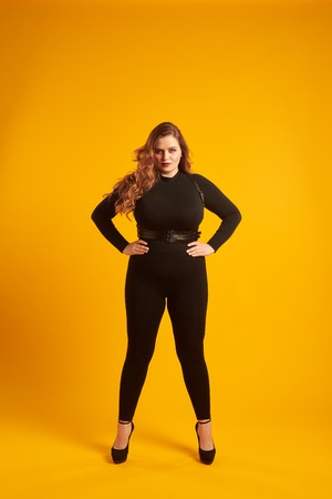 Curvy girl in tight-fitting clothes posing with her hands on hip Zdjęcie Seryjne