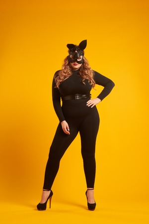 Magnetic curvy girl in bunny mask posing at studio