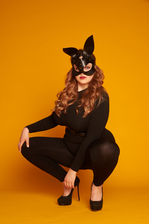 Sexy plus-size model in leather bunny mask sitting on her haunch