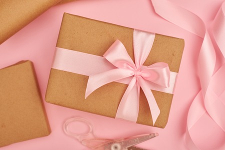 Pink satin ribbon and scissors near present box on pink flatlay Zdjęcie Seryjne