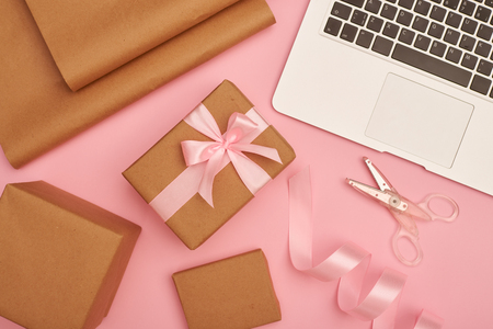 Gift wrapping set with silver laptop on pink flatlay