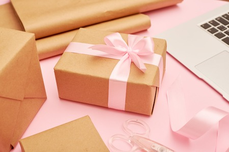 Cute present box with laptop placing on pink flatlay