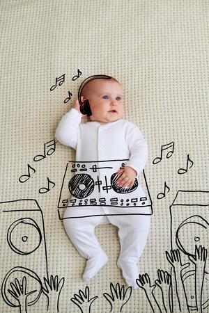 Cute DJ baby girl wearing headphones playing music at mixer