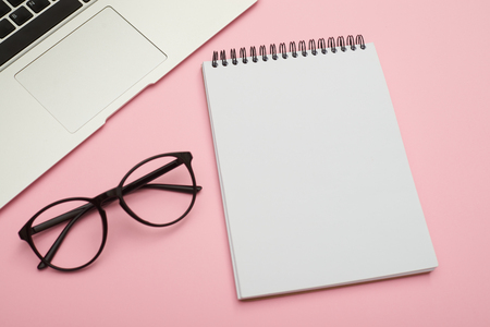 Flatlay with laptop, jotter and glasses with copyspace