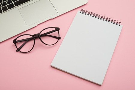 Minimalistic flat lay composition of laptop, glasses and jotter Zdjęcie Seryjne - 106935163