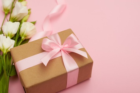 Present box with pink bow and flowers on pink background