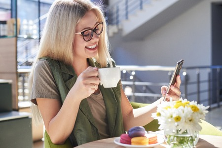 Beautiful woman using mobile phone at cafe Foto de archivo