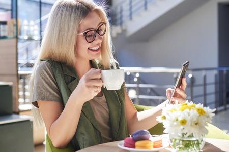 Mooie vrouw met behulp van mobiele telefoon in café Stockfoto
