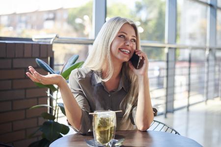 Woman talking on mobile phone at cafe Reklamní fotografie