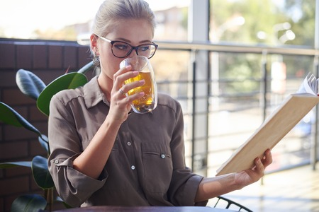 Woman reading book while drinking herbal tea at cafe Zdjęcie Seryjne - 116505446