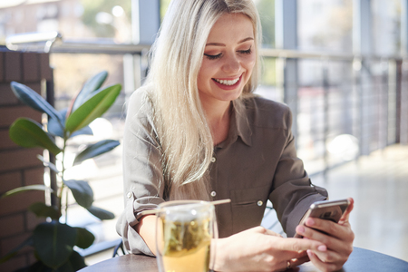 Beautiful woman using phone at cafe Zdjęcie Seryjne - 116505448