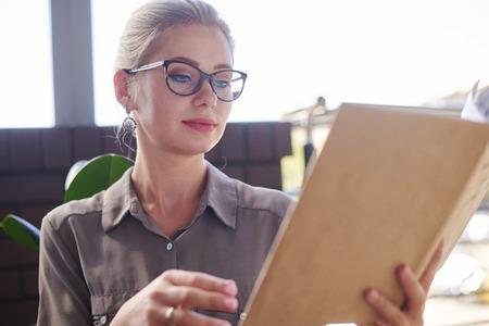Woman reading book at cafe Zdjęcie Seryjne - 116505450