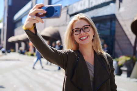 Woman taking selfie using mobile camera in city Zdjęcie Seryjne - 116505451
