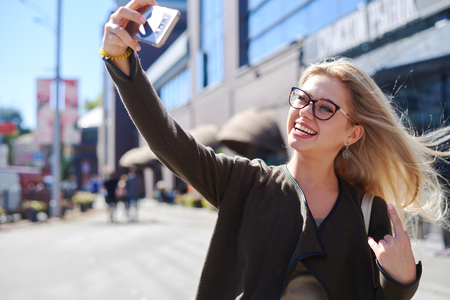 Happy woman taking selfie using mobile camera in city
