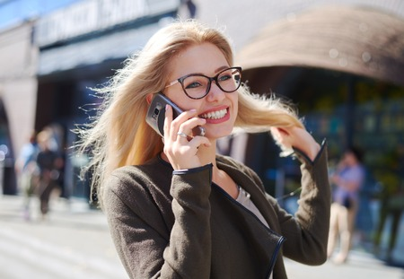 Happy woman talking on mobile phone in city Zdjęcie Seryjne - 116505455