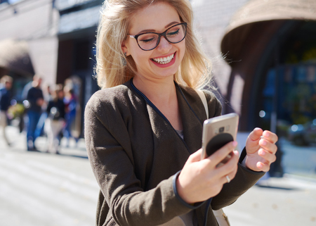 Happy woman using mobile phone in city