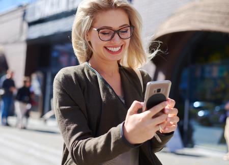 Happy woman using mobile phone in city Zdjęcie Seryjne - 116505457