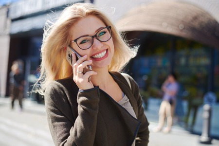 Happy woman talking on mobile phone in city Zdjęcie Seryjne - 116505465