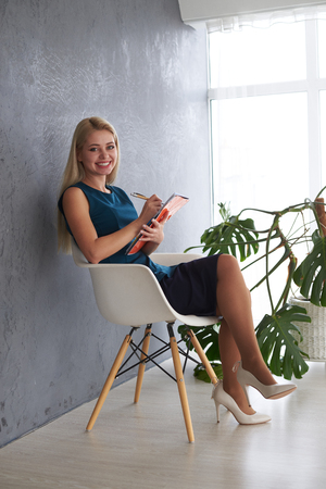 Beautiful businesswoman with file on office chair Imagens