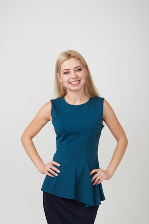 Portrait of beautiful young woman with arms akimbo against studio background
