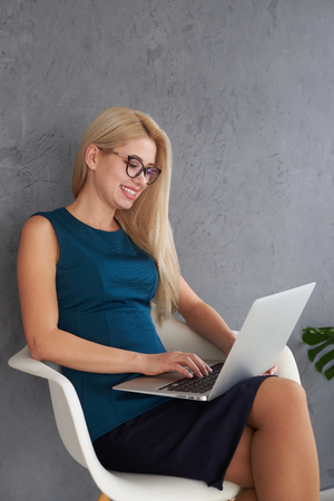 Happy businesswoman working on laptop at office