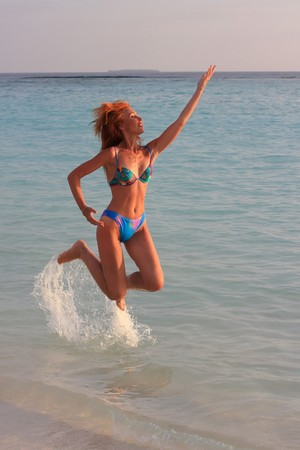 The beautiful, harmonous girl jumps in water at a beach edge photo