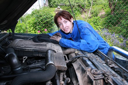 The young beautiful girl who has soiled the person and hands in lubricating oil, repairs the car photo