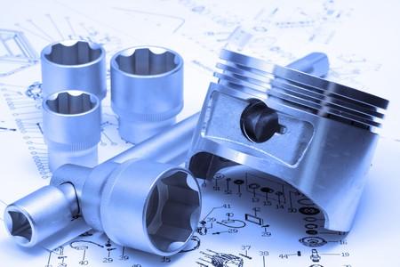 emphasizes: Piston, key, heads lay on plan, blue emphasizes industrial orientation of photo
