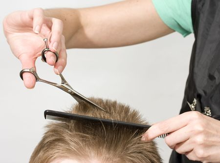 haircutting: Hairdresser cuts client with scissors
