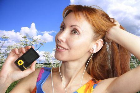Nice woman listens music in earphones and smiles photo