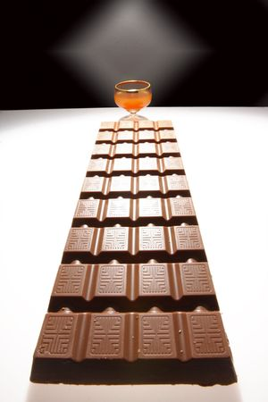 wine road: Big chocolate and wine-glass with liquor, are photographed in the form chocolate road