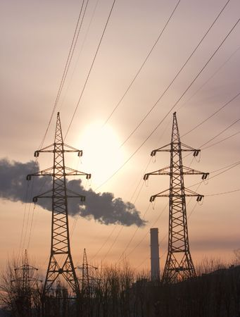 energies: Pipe with smoke and line of electricity transmission on background of city