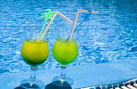 Glasses stand with cocktail on edge of pool photo