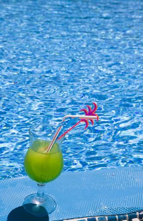 Glass stand with cocktail on edge of pool photo